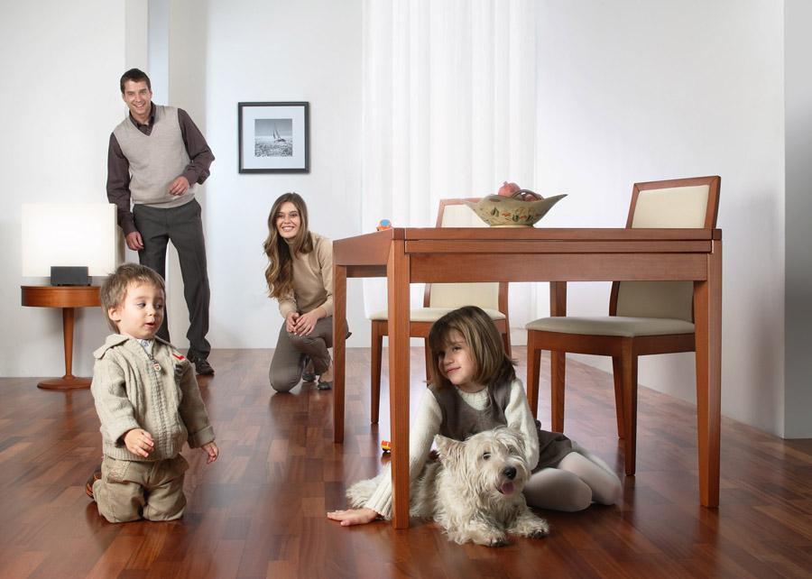 Familie care se joacă pe parchetul din lemn exotic, de culoare închisă
