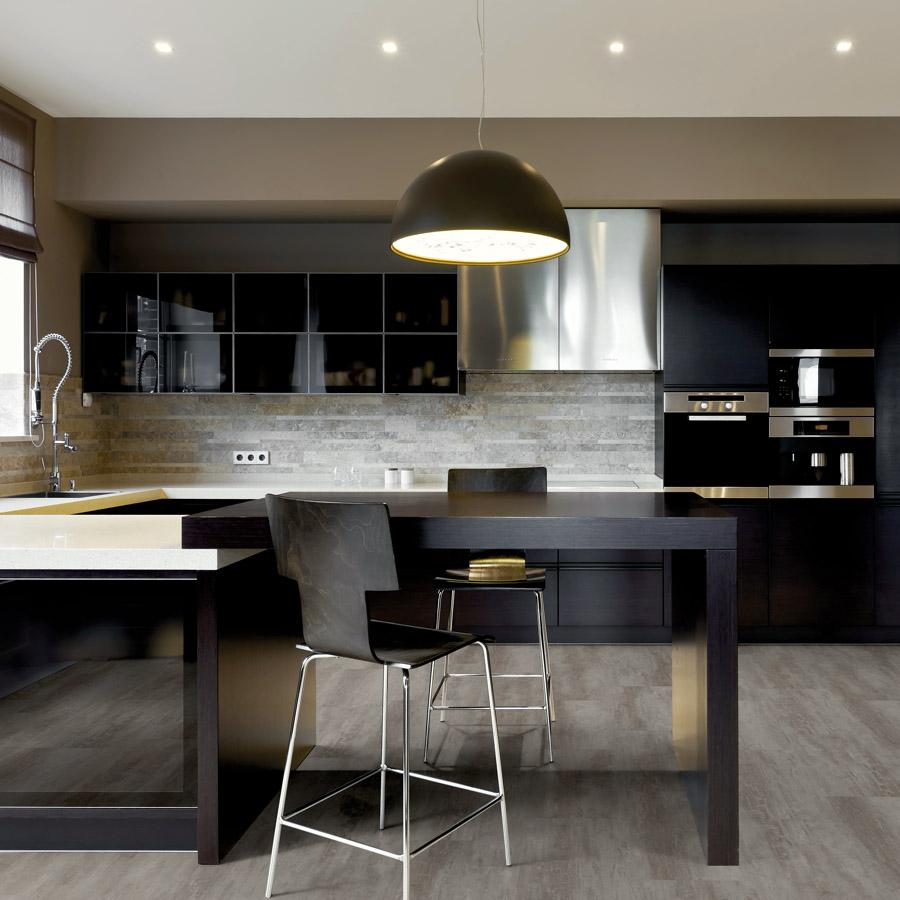 Bucătărie elegantă, modernă, în culori închise și o pardoseală LVT care imită lemnul
