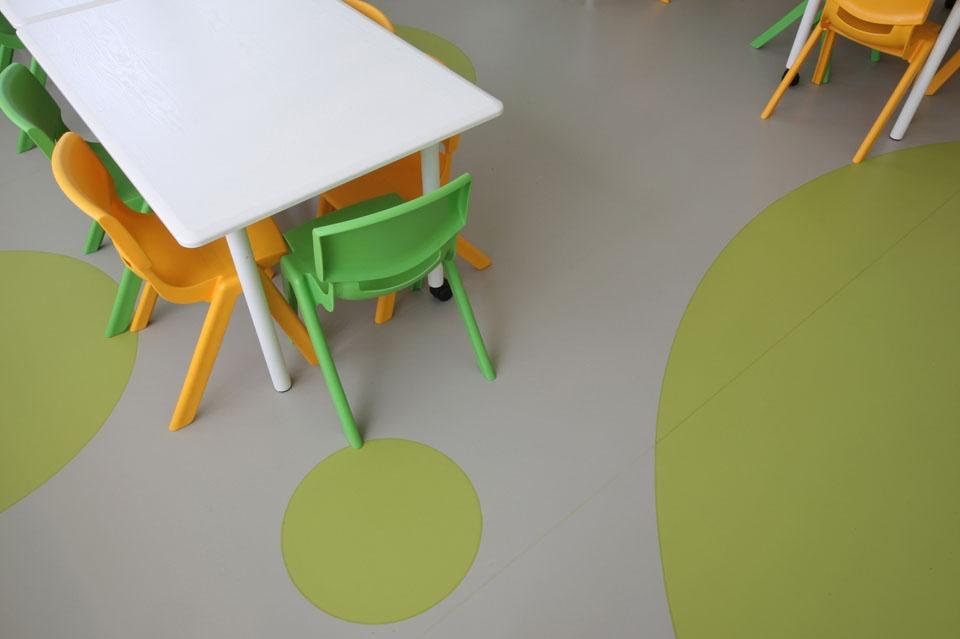 Pardoseala din linoleum, gri cu buline verzi si o masa cu scaune colorate