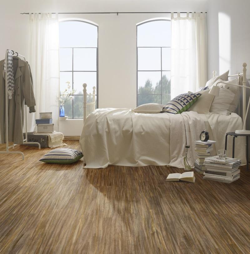 Dormitor cu pat înalt și parchet din lemn stratificat