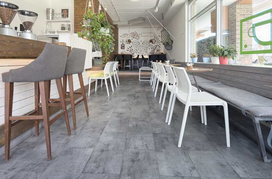 Cafeneaua Drop Caffe din Belgrad, cu masute, scaune si bar in tonuri de alb, gri si maro si o pardoseala LVT gri, asortata