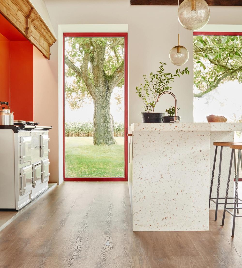 Bucătărie cu un perete portocaliu și masa cu model terrazzo