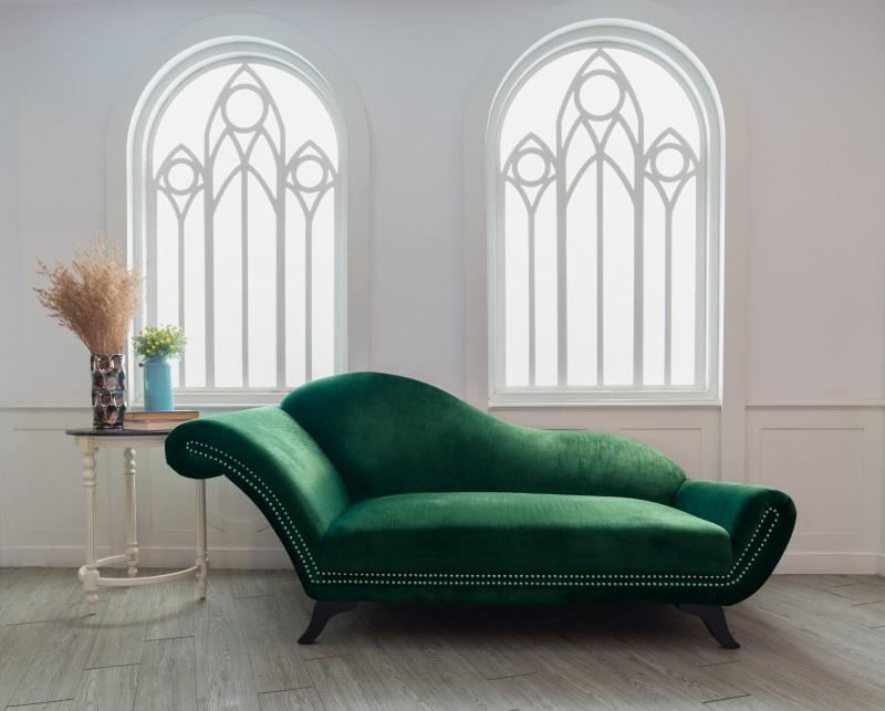 Living cu pereți albi și canapea verde, cu forme curbate