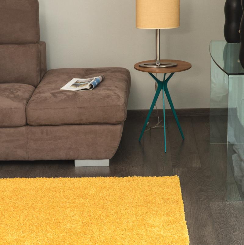 Covor galben, în living cu canapea, măsuță și veioză