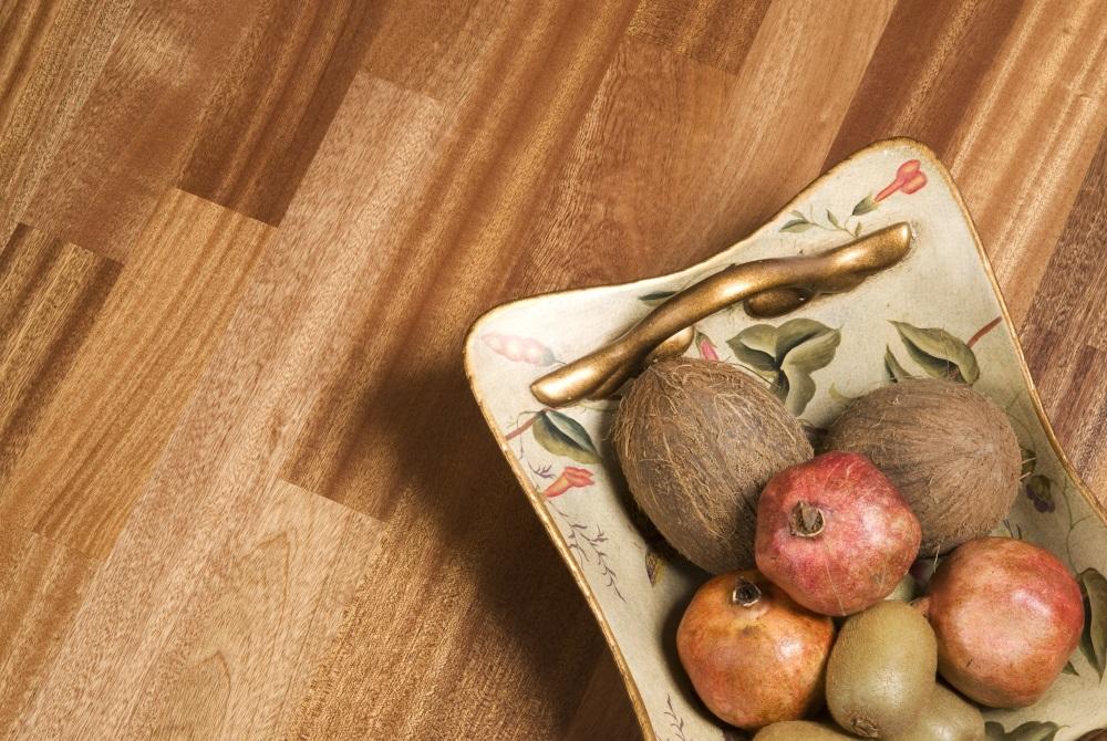 Tavă cu fructe, pe o pardoseală din parchet de mahon african