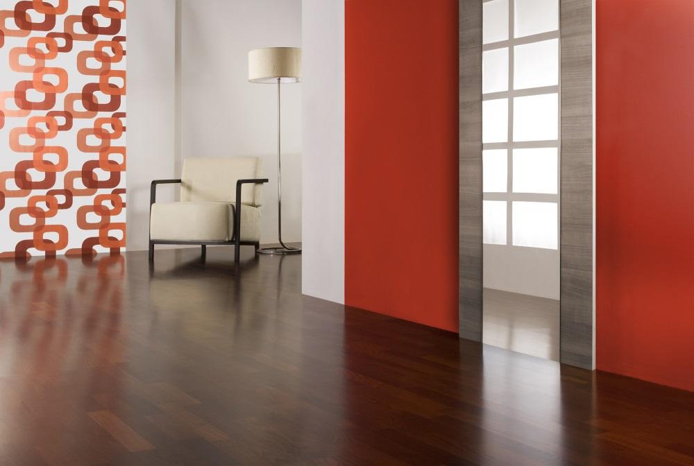 Parchet maro roșcat în living decorat cu mult roșu