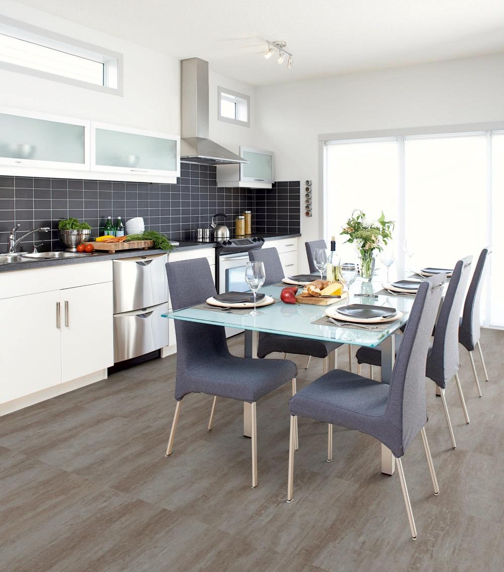Bucătărie spațioasă și luminiasă, cu masă în mijloc, amenajată cu pardoseală din LVT