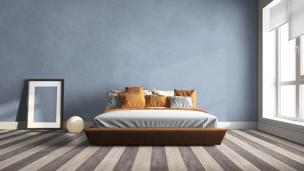 Dormitor spațios, cu pat mare, perete albastru și pardoseală LVT în dungi