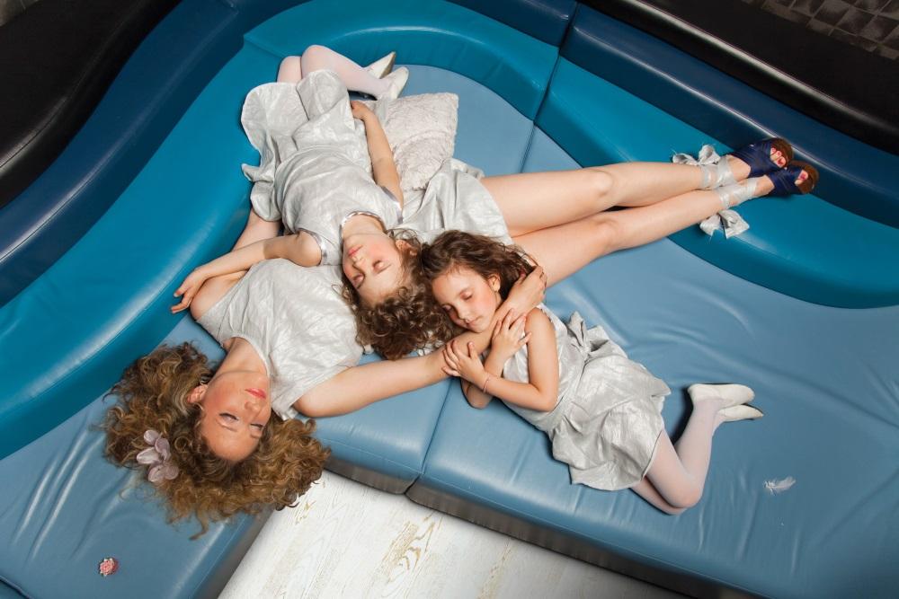 Mama și două fiice dorimind pe o canapea în 3 nuanțe de albastru