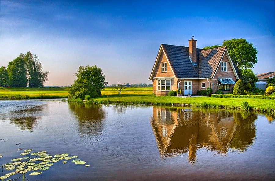 Cabană în câmp, pe malul lacului, la apus