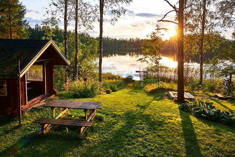 Cabană pe malul lacului, la apus