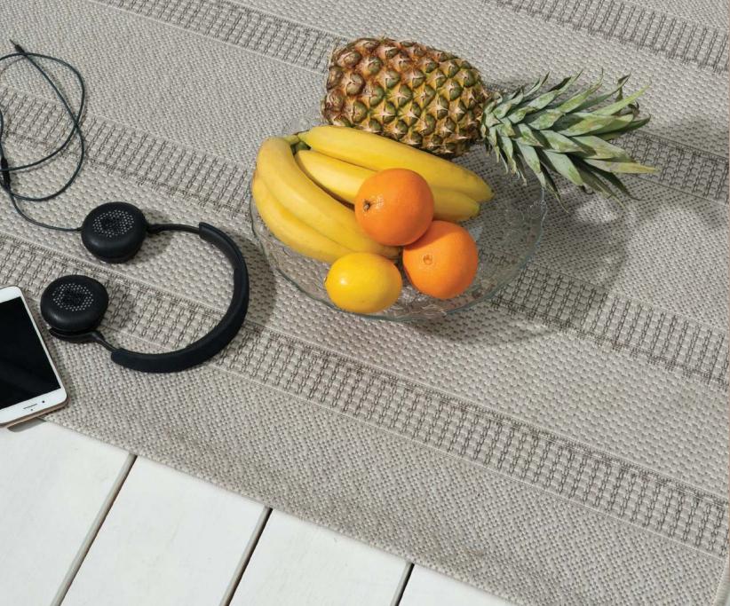 Covor gri cu dungi pe parchet alb și platou cu fructe