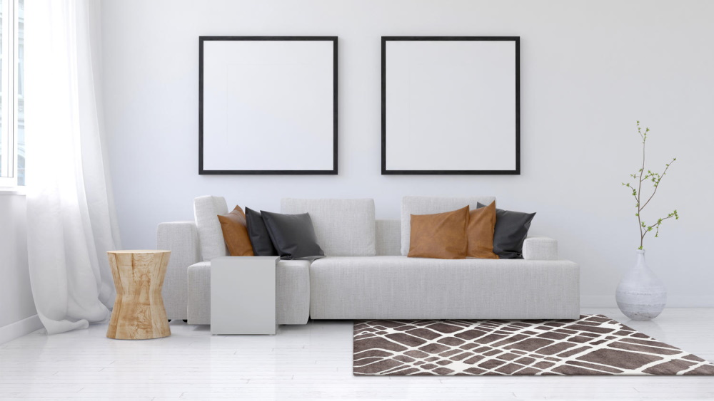 Covor maro cu alb, în living cu canapea albă și două tablouri albe pătrate, cu ramă neagră